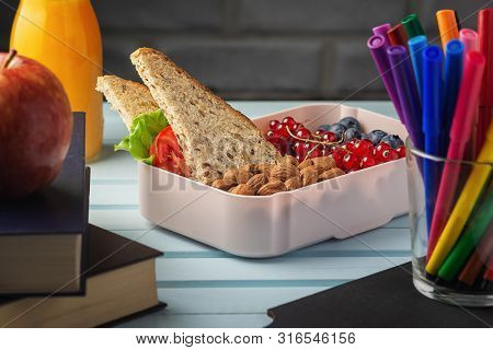 Healthy Food For School Lunch. On The Table Among The Textbooks Is A School Lunch, In A Box Are Almo