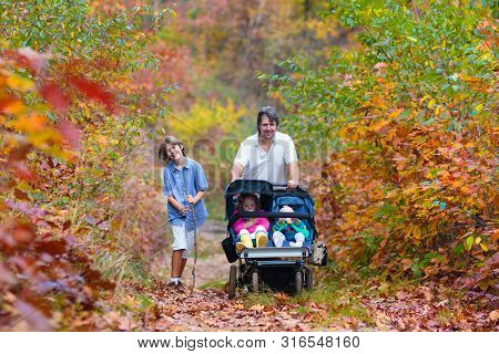 Family Hiking With Stroller In Autumn Park. Active Mother, Baby And Toddler In Twin Double Pushchair