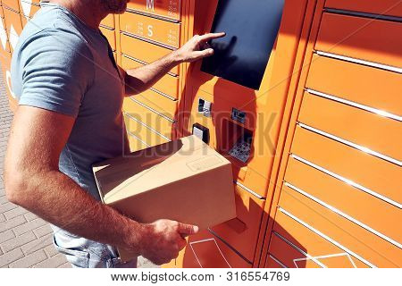 Man Using Automated Self Service Post Terminal Machine Or Locker To Deposit The Parcel For Storage