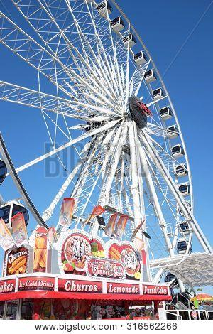 COSTA MESA, CALIFORNIA - AUG 8, 2019: Ferris Wheel and Funnel Cake vendor at the Orange County Fair.