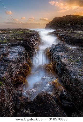 Dramatic Seascape Shot With Long Exposure Of An Exposed Rock At Low Tide With The Sunrising In The D