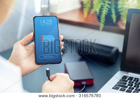Woman Charges Her Smartphone With Power Bank Using Fast Charge  Usb-c Cable. Interface On The Screen