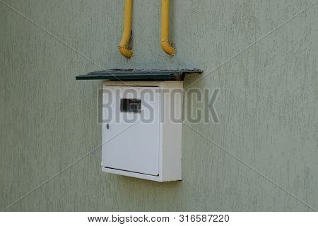 White Gas Meter With Yellow Pipes On A Gray Wall