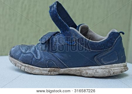 One Old Blue And Dirty Sneaker Stands On A White Table