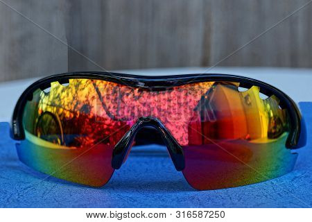 One Colored Sunglasses Lie On A Blue Table