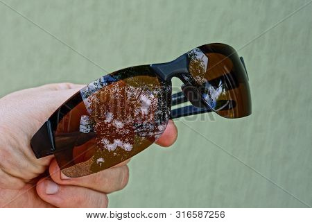 Hand Holds One Brown Sunglasses On Gray Background