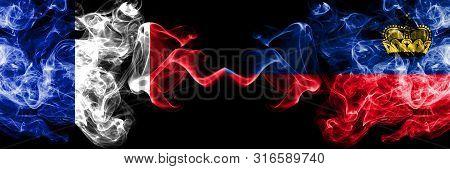 France Vs Liechtenstein, Liechtensteins Smoky Mystic Flags Placed Side By Side. Thick Colored Silky