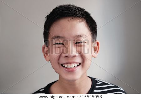 Portrait Of Happy, Confiden And Healthy Asian Preteen Teenage Boy Smiling