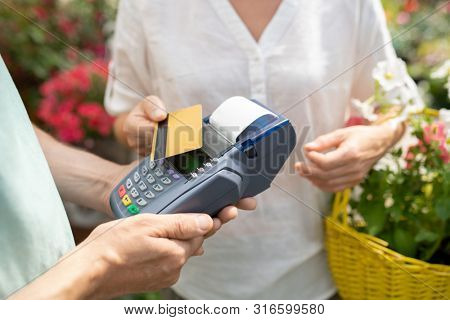 Contemporary female buyer using credit card to pay for some fresh potted flowers