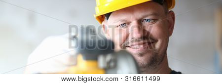 Portrait of smiling builder using modern power equipment in order to make work easier. Smart guy holding electric saw carefully and joyfully. Building concept poster