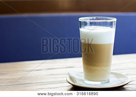 Latte Glass On The Table On The Terrace Of The Summer Cafe.  Hot Latte Glass On A Wooden Table.  Sun