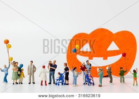 Miniature People:  Happy Family Holding Balloon On White Background