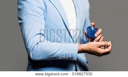 Man Perfume, Fragrance. Masculine Perfume. Man Holding Up Bottle Of Perfume. Fashion Cologne Bottle.