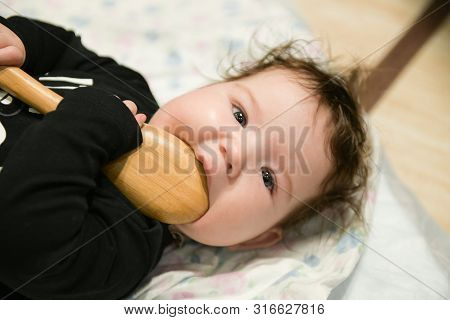 The Kid Nibbles A Wooden Spoon. Newborn Is Nibbling A Wooden Spoon On The Bed. Itchy Teeth