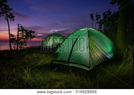 Green Illuminated From Inside Tent Above River At Sunset.