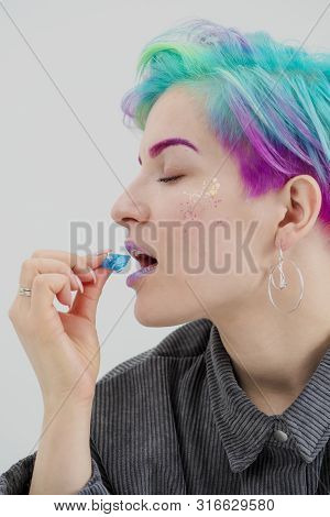 A Young Woman With Short Pixie Bob Haircut And Dyed Hair, Holds In The Mouth And In The Hands Gemsto