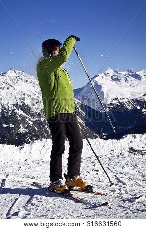 Man In Green Jacket Enjoying Skiing In Winter Apls.