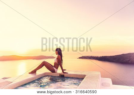 Luxury resort vacation bikini model woman relaxing lying down by hot tub private swimming pool hotel room suite balcony sunset over the Aegean sea in the Cyclades islands, Santorini, Greece.