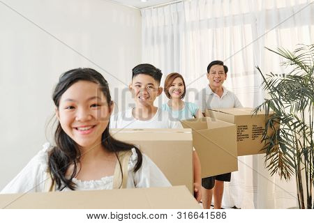 Smiling Vietnamese Family Members With Cardbord Boxes Standing One Behind Another And Looking At Cam