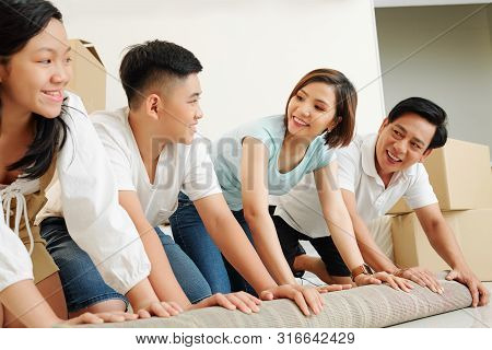 Happy Vietnamese Parents And Children Looking At Each Other When Unfolding Carpet In Their New Apart