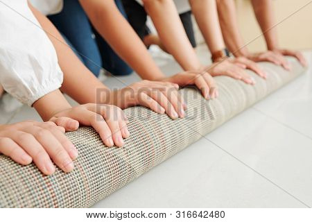 Close-up Up Image Of Of Big Family Unfolding Carpet In Their New House After Moving In