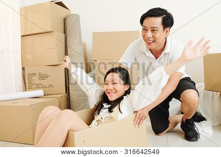 Mature Asian Man Pushing Box With His Pretty Preteen Daughter Sitting Inside After They Moved In New