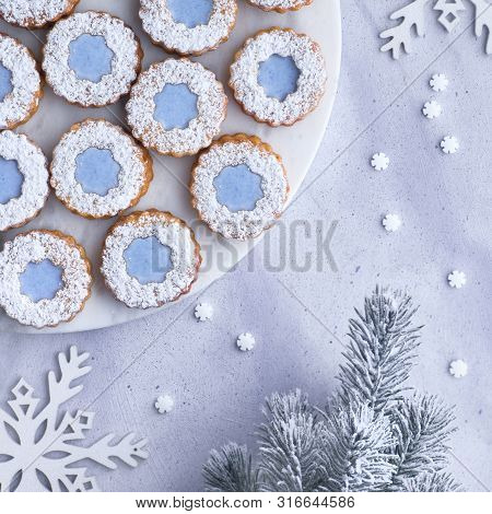 Flower Linzer Cookies With Blue Icing On White Marmor Board Set On Top Of Light Winter Background Wi