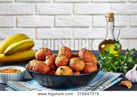 Close-up Of Deep Fried Plantain Fritters Klako In A Black Bowl With Ingredients And Brick Wall At Th