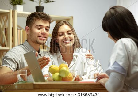 Smiling Nutritionist Showing A Healthy Diet Plan And Fruits To Patient. Young Couple Visiting A Doct
