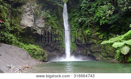 Waterfall In Green Rainforest. Tropical Tuasan Falls In Mountain Jungle. Waterfall In The Tropical F