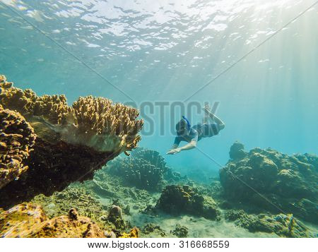 Happy Man In Snorkeling Mask Dive Underwater With Tropical Fishes In Coral Reef Sea Pool. Travel Lif