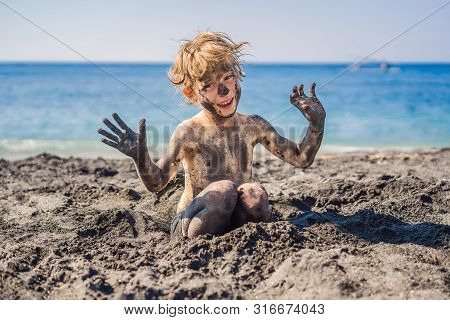Black Friday Concept. Smiling Boy With Dirty Black Face Sitting And Playing On Black Sand Sea Beach