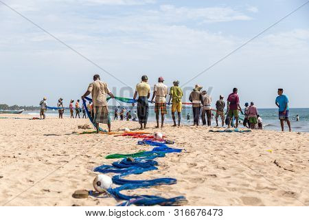 Trincomalee, Sri Lanka - August 20, 2018: Group Of Fishermen Hauling In A Big Fishing Net At Uppuvel
