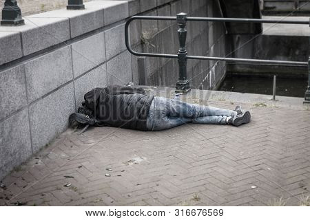 A Homeless Man Lying On The Street