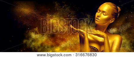 Gold Christmas Woman. Beauty fashion model girl with Golden make up, hair and jewellery, pointing hand on black background with magic dust. Glowing skin. Metallic, glance Fashion art portrait, make up