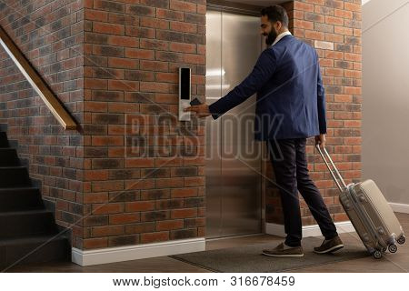 Delighted Bearded Male Person Waiting For Elevator