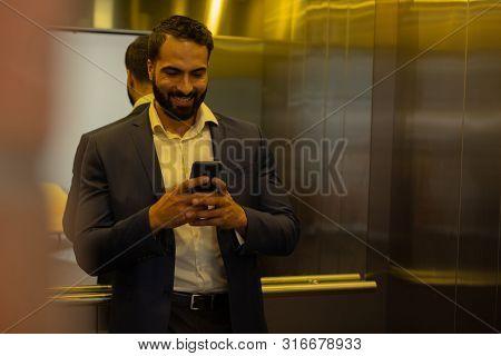 Joyful Brunette Male Person Reading Funny Message