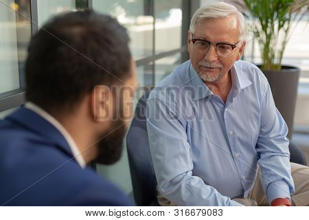 Handsome Grey-haired Man Looking At His Colleague
