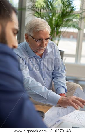 Concentrated Bearded Mature Man Pointing At Computer