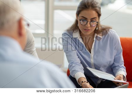 Attentive Brunette Woman Looking At Pale Of Documents
