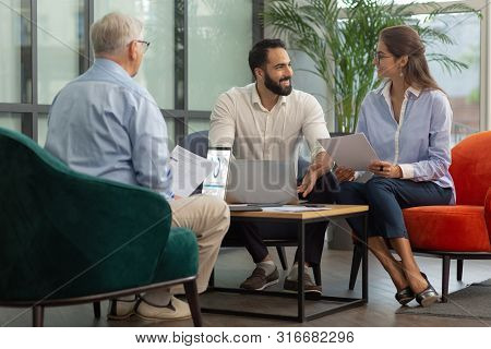 Positive Delighted Bearded Man Looking At His Colleague
