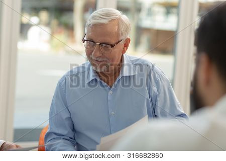 Attentive Grey-haired Male Person Looking At Documents