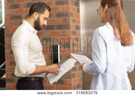 Young Office Workers Waiting For Elevator Together