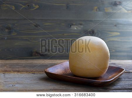 Round Head Of Cheese Kostromskoy On Textured Dark Wooden Background On The Square Plate. Horizontal