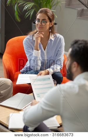 Positive Delighted Female Person Listening To Presentation