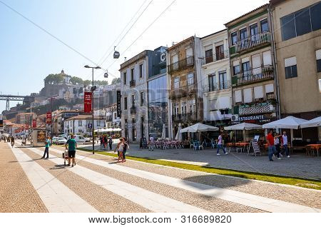 Porto, Portugal - August 31 2018: People Walking On Promenade By River Douro On A Sunny Day. The Emb