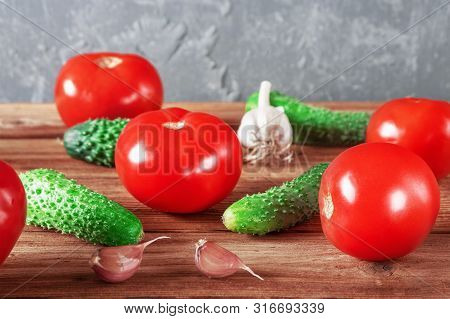 Red Fresh Tomatoes, Garlic And Green Cucumbers On Wooden Background