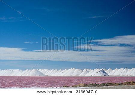 Piles Of White Salt Next To Pink Salt Flats On The Caribbean Island Of Bonaire