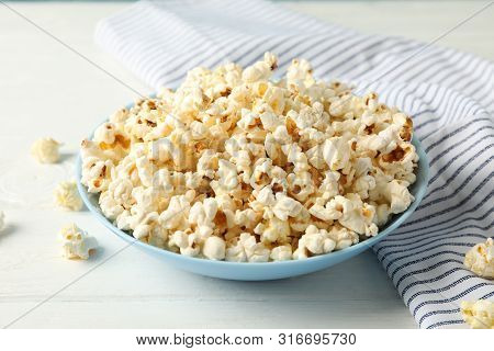 Towel And Plate With Popcorn On White Wood Background, Copy Space