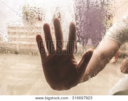 Human Hand Pressed Against A Window With Drops Of Rain On It. Hand Touching Clear Glass With Water D